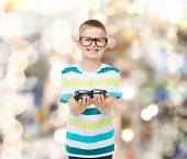 vision, health and people concept - smiling little boy in eyeglasses holding spectacles over sparkli