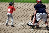 Baseball player batting with umpire behind fence