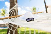 vacation and holiday concept - picture of hammock with white hat and sunglasses