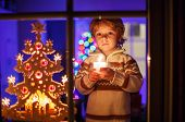 Cute Toddler Boy Standing By Window At Christmas Time And Holding Candle
