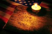 the sentence we do not forget you carved on wooden and the flag of the United States and a lighted c