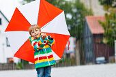image of rainy season  - Smiling little boy walking in city with red umbrella wearing colorful rain coat and green boots outdoors at rainy day - JPG