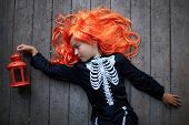 Portrait of cute girl in red wig and Halloween costume holding lantern