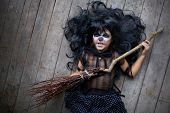 picture of warlock  - Grinning girl in black wig holding broom and looking at camera - JPG