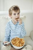 Boy watching TV while eating wheel shape snack pellets