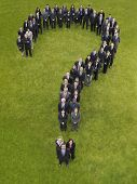 Large group of business people standing in question mark formation, elevated view