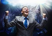 Cheerful businessman with hands up celebrating success