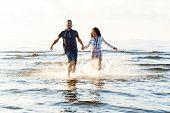 Summer, love. Attractive couple running on the beach