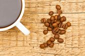 Close Up Of White Ceramic Coffee Cup With Roasted Coffee Beans On Wooden Table - View From Top