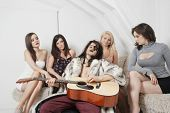 Young man playing guitar amid female friends