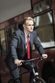Young businessman riding bicycle by bus
