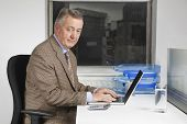 Portrait of middle-aged businessman using laptop at desk in office