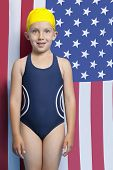 Portrait of a young girl in swimwear standing in front of American flag