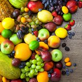 Mix of Fresh Organic Fruits  with water drops on wooden table background - Healthy Eating