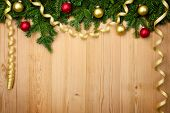 Christmas background with fresh firtree, baubles and ribbons on wood - horizontal