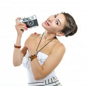 Beautiful excited girl takes picture with retro photo camera, over white.