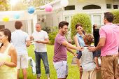 Multi Generation Family Enjoying Party In Garden Together