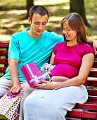 Pregnant woman, holding shopping bag with man outdoor.