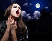 Vampire woman on night background with moon