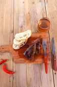 fresh beef meat steak with red hot pepper and bun slices served on plate with whiskey on wood over t