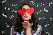 Young Woman Blowing Kiss With Heart Shape Paper Sticker Covered On Eyes On Blackboard