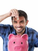 stock photo of spanish money  - young happy man wearing casual shirt holding coin putting it into pink piggy bank in saving money financial and banking concept isolated on white background - JPG