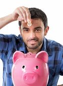 Young Happy Man Holding Coin Putting It Into Pink Piggy Bank