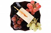 cream cake and grapes on black plate