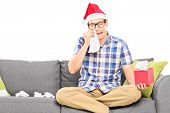 Sad man with Santa hat wiping his eyes from crying isolated on white