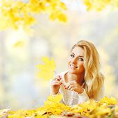 Cheerful young woman laying down on the ground covered with dry autumnal foliage in beautiful park