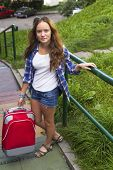 Young beautiful girl and red suitcase outdoors, travel concept.