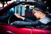 young urban fashion woman driving red cabrio through the city