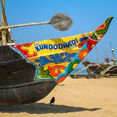 GOA, INDIA - JANUARY 21, 2013: Painted wooden fishing boat on the sandy shore in Goa, India
