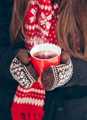 cup of hot tea, women's hands in mittens on a background of a Christmas scarf, close-up