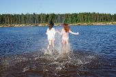 Two young girls run to the river