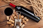 Red wine bottle, glass, corks and corkscrew. View from above over rustic wooden table background