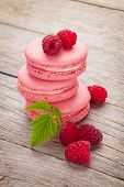 Pink raspberry macaron cookies on wooden table background