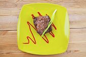 meat savory : grilled beef fillet mignon served on green plate over wooden table with chives and ketchup
