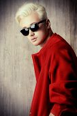 Portrait of a fashionable male model with blond hair wearing red coat and black sunglasses. Men's beauty, fashion.