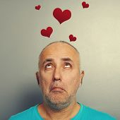 amazed senior man looking up at small red hearts over grey background