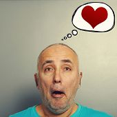 portrait of amazed senior man and drawing speech bubble with red hearts over grey background