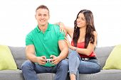 Girl watching her boyfriend play video game seated on a sofa isolated against white background