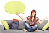 Woman holding a speech bubble seated on a sofa isolated against white background