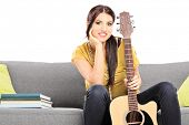 Beautiful female guitarist sitting on a sofa isolated against white background