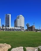 TEL AVIV, ISRAEL - MAY 2, 2014: The picturesque Tel Aviv embankment in sunny spring day. Modern magnificent hotels - skyscrapers and green lawns