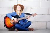 woman in a hat plays guitar sitting on the floor
