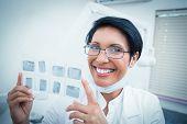 Portrait of happy female dentist holding x-ray