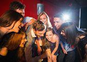 Happy friends singing karaoke together in a bar