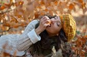 young woman eating apple outdoor in autumn