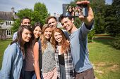 Happy students taking a selfie outside on campus at the university